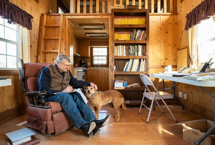 John R. Erickson sitting in a chair writing in his cabin while petting his dog Rosie.